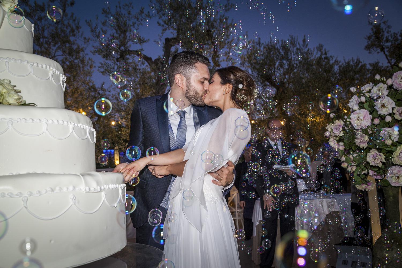 bacio degli sposi al taglio della torta con bolle di sapone fotografia matrimonio napoli