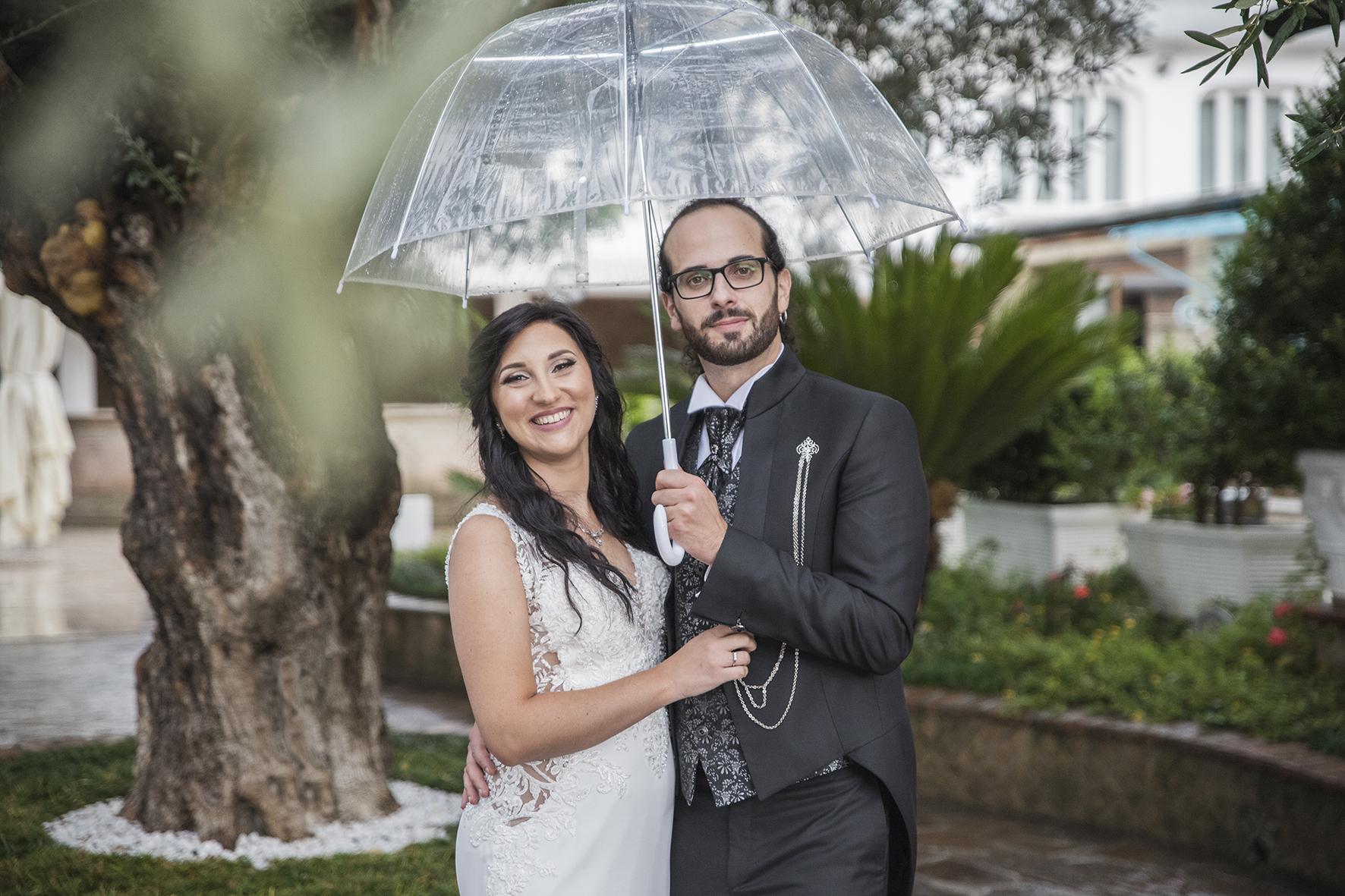 sposi con l ombrello sotto la pioggia